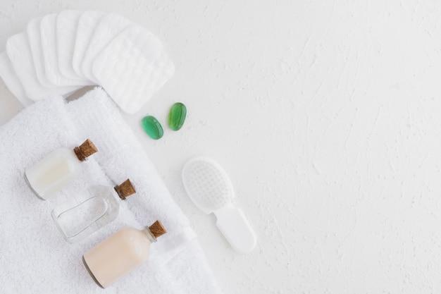 Prodotti da bagno su un asciugamano con dischetti di cotone e copia spazio
