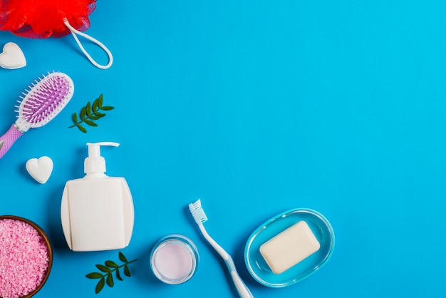 Bath products with salt; toothbrush; sponge and hairbrush on blue background