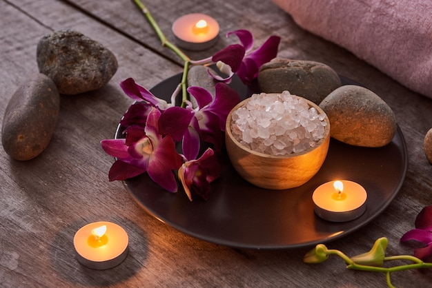Соль для ванн в бамбуковой чаше и цветы орхидеи на темном дереве