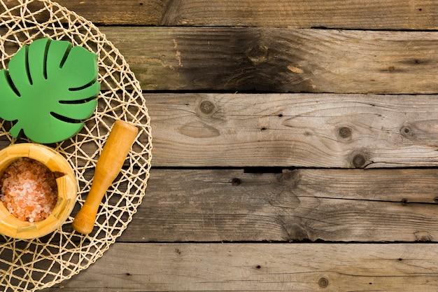 Соль для ванны в ступке с пестиком и деревянным листом на столе