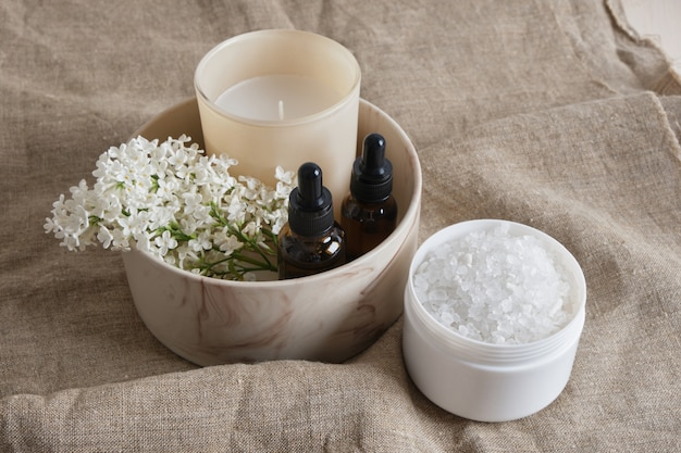 Bath salt, white lilac, aroma candle and brown bottles with pipettes with aroma oil in a ceramic bowl on a natural linen background copy space
