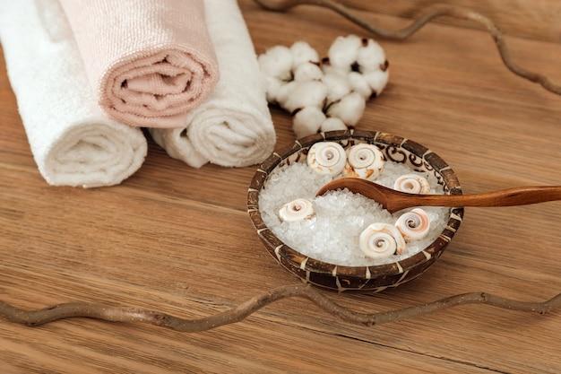 Установка спа-ванны с морской солью в миске и мягким полотенцем на коричневом деревянном