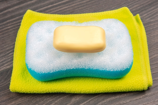 Bath sponge, soap and towel on wooden background