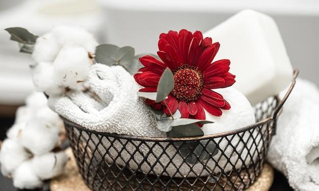 バスタオルとバスボムと赤い花。衛生と健康の概念。
