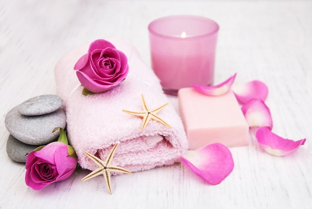 Bath towels, candle and soap with pink roses