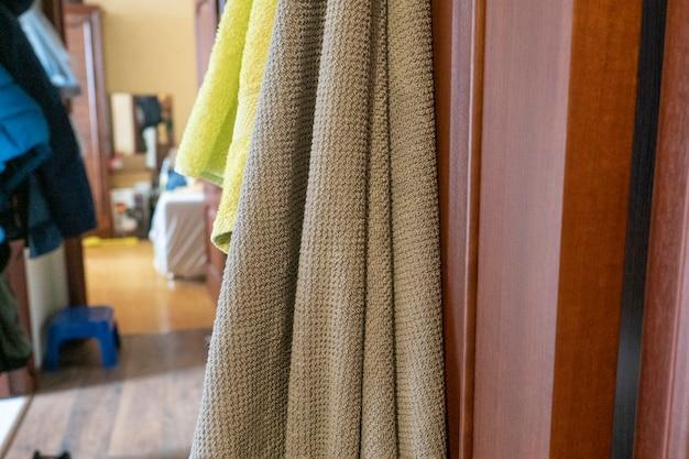 Банные полотенца вешают на открытую дверь. размытый фон интерьера комнаты на заднем плане