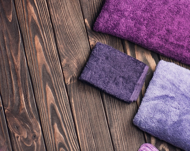 Bath towels on wooden background. blue and purple bath towel