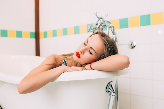 幸せな笑顔のバスフォームとバスタブを楽しんでいるお風呂の女性。混血のアジア人/白人女性モデルのバスルーム。