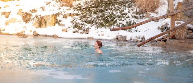 사우나 후 얼어 붙은 호수에서 젊은 여자 목욕
