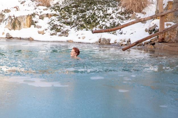 サウナの後、凍った湖で若い女性を入浴します。