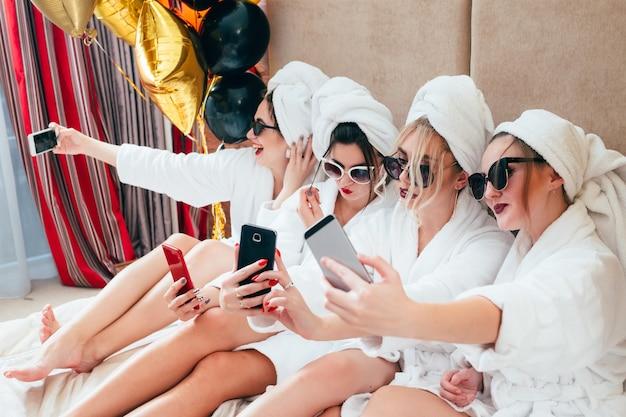 バスローブガールズパーティー。サーフィンソーシャルメディア。自分自身、喜び、そして楽しさを共有する。サングラスとタオルターバン
