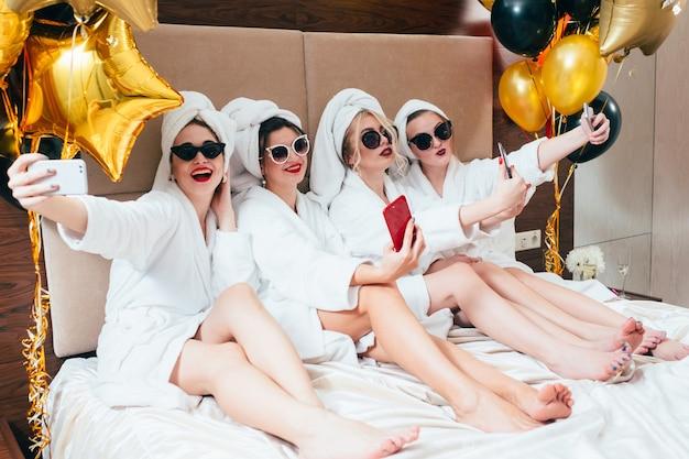 自撮りをしているバスローブパーティーの女の子。女性のレジャーとライフスタイル。サングラスとタオルターバン Premium写真