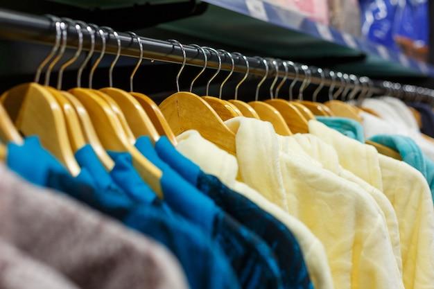 店内のハンガーにぶら下がっているさまざまな色のバスローブのクローズアップ、ソフトフォーカス