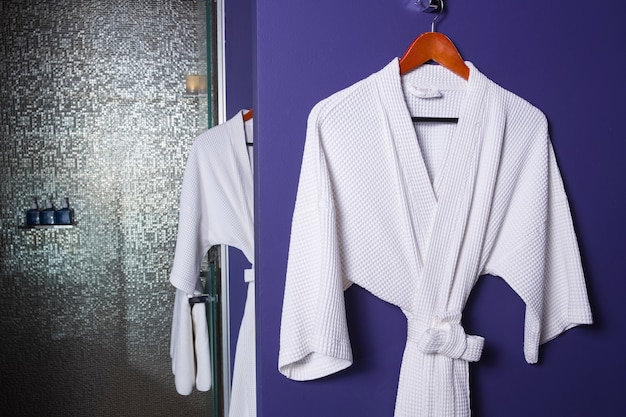 Bathrobes hanging on hook against wall in hotel.