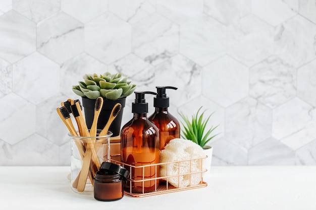 욕실 액세서리, 천연 화장품, 욕실 배경 안에 있는 흰색 테이블에 녹색 식물이 있는 도구.