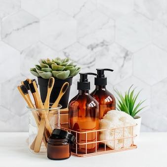 浴室の付属品、自然化粧品、浴室の背景の白いテーブルに緑の植物とツール。