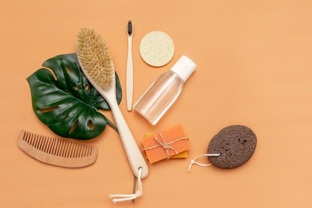 Аксессуары для ванных комнат с безотходной расческой, деревянной зубной расческой, твердым мылом, косметической банкой, деревянной расческой, губкой с листом монстеры на бежевом фоне.