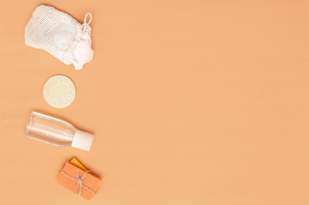 제로 폐기물 스폰지, 고체 비누 막대, 베이지색 배경에 화장품 병이 있는 욕실 액세서리