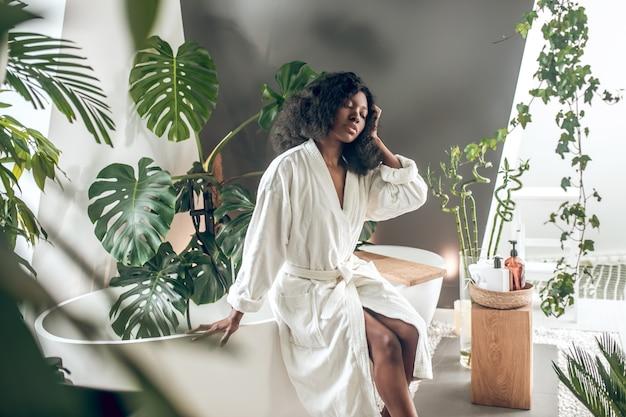 In a bathroom. african american prety woman in a white robe in a bathroom