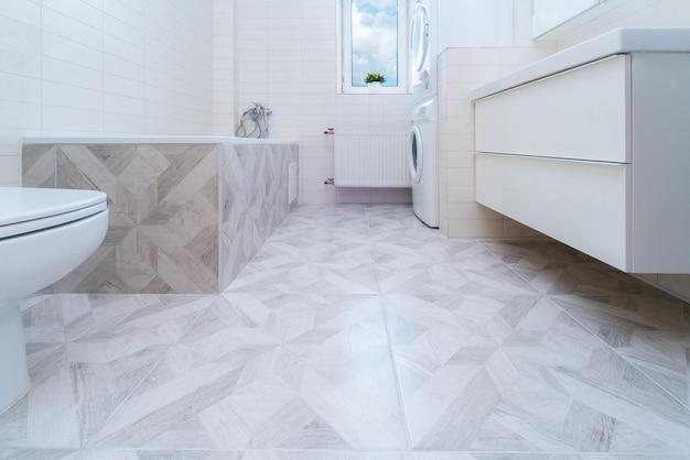 리모델링 후 욕실입니다. 욕실 바닥에 새로운 석재 타일. 주택 개조 및 개선 개념입니다. 아무도