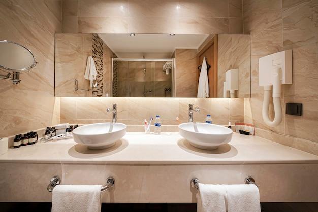 バスルームとシャワールームの鏡。ベージュのインテリア、敷地内のインテリアデザイン。タオル。