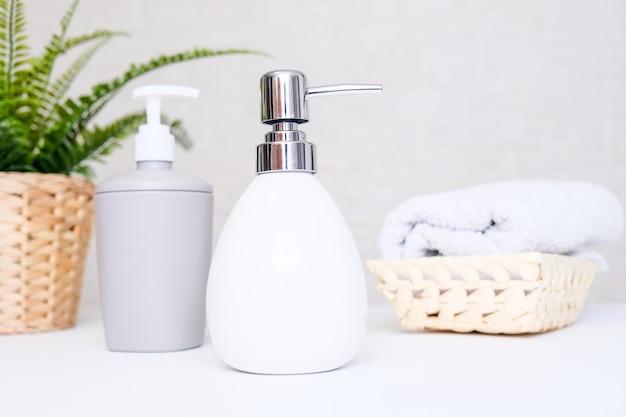 Фон для ванной комнаты, туалетные принадлежности для ухода за руками и телом, дозатор жидкого мыла и полотенца на светлом фоне.