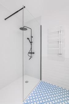 浴室采用淡蓝色和白色瓷砖装饰,带有大雨头、手持式淋浴和玻璃门的现代淋浴区