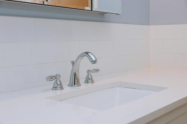 Элегантный интерьер ванной комнаты с раковиной и краном.