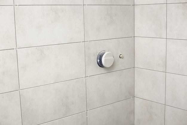 きちんとした長方形のパターンとビルトインシャワーを備えたバスルームの灰色のタイル。バスルームタイルテクスチャ。修復。