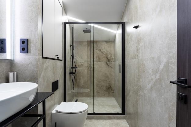 Ванная комната в традиционном стиле с коричневыми и серыми стенами. минималистичная душевая с сауной отеля.