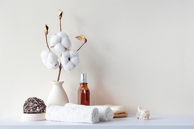 Bathroom interior in beige pastel tone. white shelf in bathroom with towels, soap, perfume bottle, cotton plant. mockup with space for text. minimal composition.