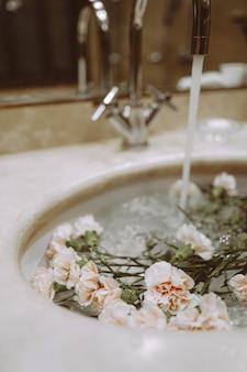 Детали интерьера ванной комнаты с цветами в раковине. эстетическая красота