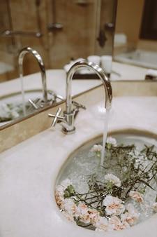 Детали интерьера ванной с цветами в раковине