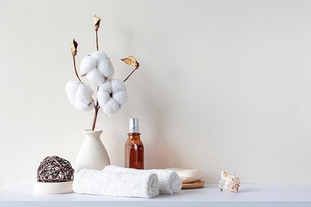 Интерьер ванной в бежевых пастельных тонах. белая полка в ванной с полотенцами, мылом, флаконом для духов, хлопком. макет с пространством для текста. минимальный состав.