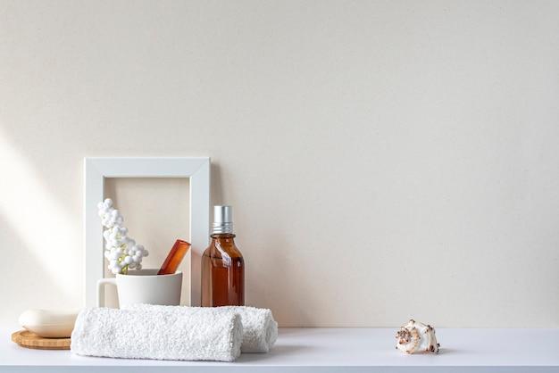 Интерьер ванной в бежевых пастельных тонах. белая полка в ванной с полотенцами, мылом, флаконом для духов, расческой, комнатным растением. макет с пространством для текста. минимальный состав.