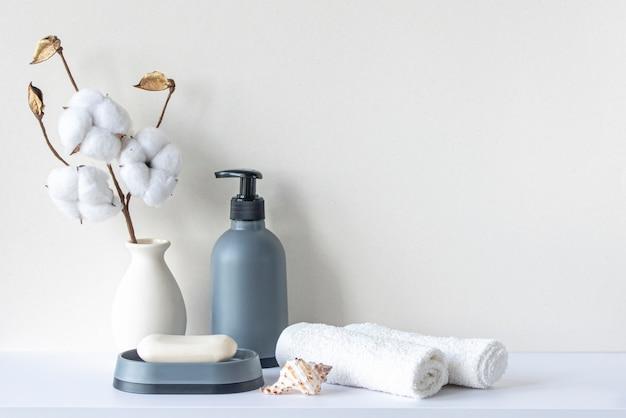 수건 비누 샴푸 병이 있는 욕실의 베이지색 파스텔 톤 흰색 선반의 욕실 인테리어 프리미엄 사진