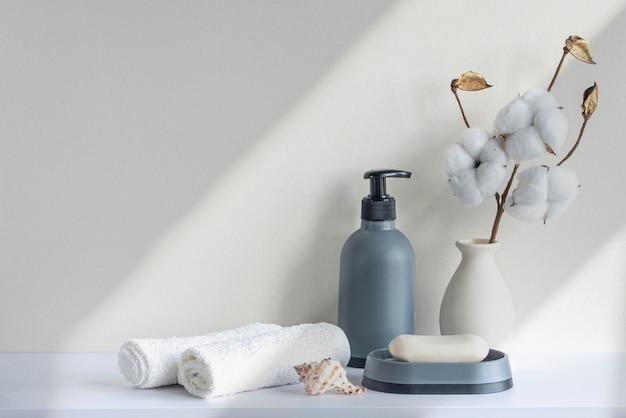 수건 비누 샴푸 병이 있는 욕실의 베이지색 파스텔 톤 흰색 선반의 욕실 인테리어