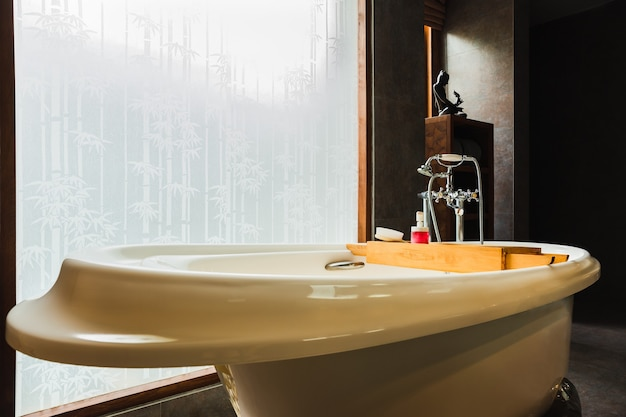 Интерьер ванной комнаты класса люкс в современном стиле с ванной и окном.