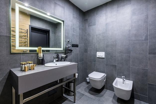 Интерьер ванной комнаты с красивой керамической плиткой и душевой кабиной серого темного цвета
