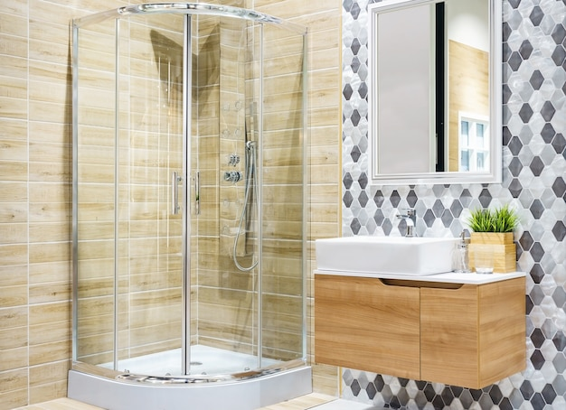 Bathroom interior with a shower cabin with glass wall, a toilet and faucet sink
