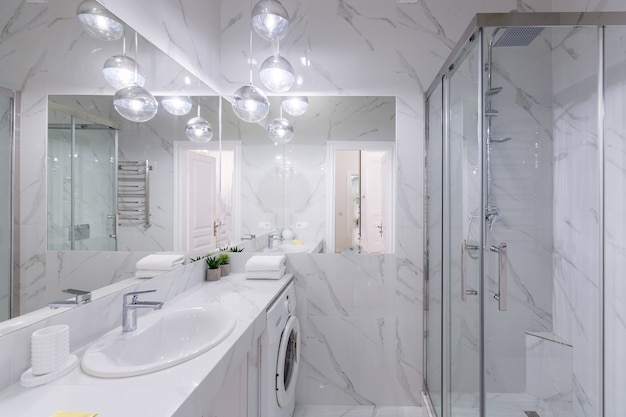 Bathroom interior with white marble tiles and modern style shower