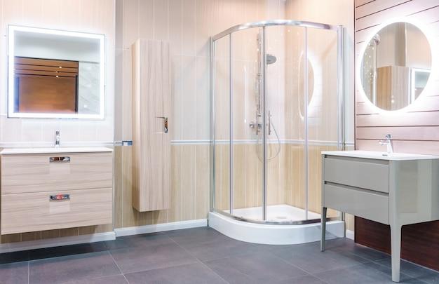 Интерьер ванной комнаты с белыми стенами, душевая кабина со стеклянной стеной, туалет и раковина