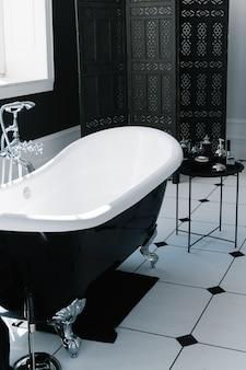 Интерьер ванной комнаты с окнами и ванной с ножками