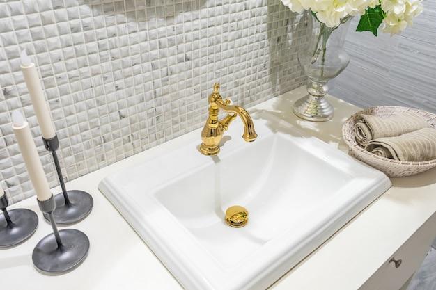 白いシンクと古典的なレトロなスタイルの黄金の蛇口のバスルームの豪華なクラシックインテリア