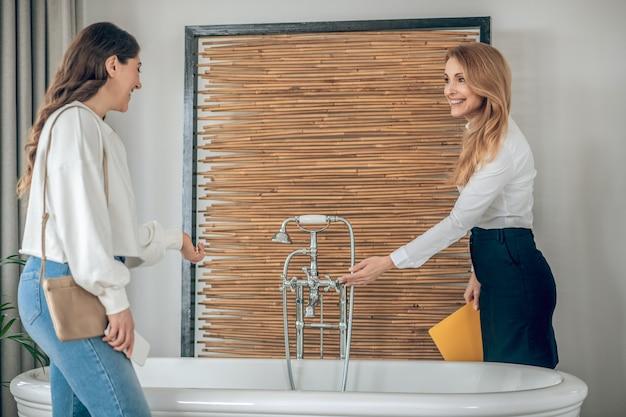 화장실. 여성 고객에게 화장실을 보여주는 부동산 중개인