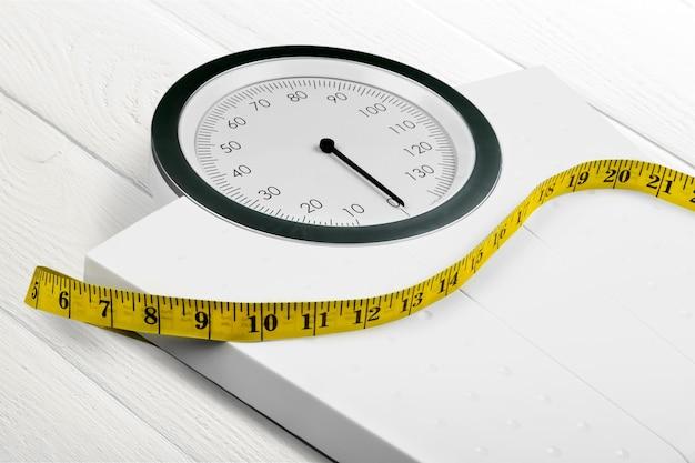 背景に巻尺が付いている体重計