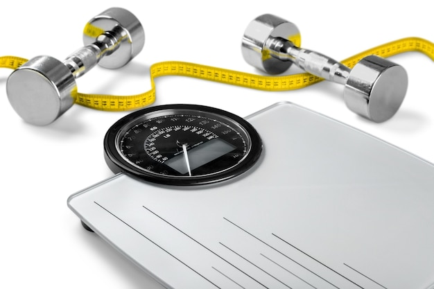 Bathroom scale with a measuring tape and dumbbells on background