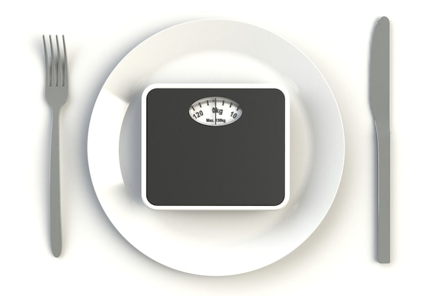 Bathroom scales on plate, knife and fork on white
