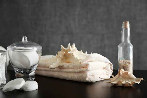 Bathroom set with shells, towel and sponges on grey table
