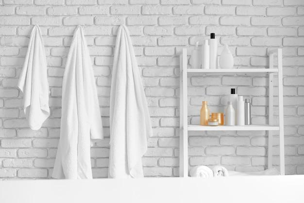 Стеллажи для ванной с косметическими бутылками и белыми висячими полотенцами на фоне белой кирпичной стены